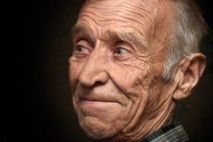 Gladlynt äldre man på en svart bakgrund Arkivbild