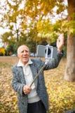 Gladlynt äldre man som gör selfie på en mobiltelefon med en monopod Utomhus på gatan royaltyfri foto