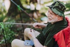 Gladlynt äldre man som tycker om att fiska på helgen arkivfoto