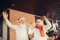 Gladlynt äldre par som bär röda lock för jul royaltyfria bilder