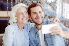 Gladlynt åldrig kvinna och hennes sonsondanandeselfies Royaltyfria Bilder
