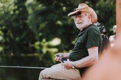 Gladlynt åldrig man som tycker om hans fiska helg arkivbild