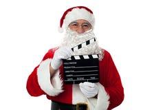 Gladlynt åldriga Santa som poserar med en clapperboard fotografering för bildbyråer
