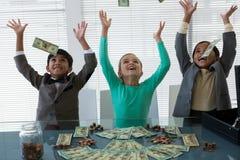 Gladlynt affärsfolk som kastar valuta i luft royaltyfri bild