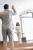 Gladlynt affärskvinna med bagage som går in mot den manliga kollegan i konventcentrum Royaltyfria Bilder