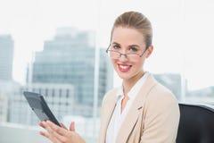Gladlynt affärskvinna med exponeringsglas genom att använda räknemaskinen arkivfoton