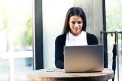 Gladlynt affärskvinna som använder bärbara datorn i kafé Arkivbilder