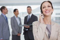 Gladlynt affärskvinna som kallar medan kollegor som tillsammans talar Arkivbilder