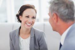 Gladlynt affärskvinna som lyssnar till hennes jobbarkompissamtal arkivfoto