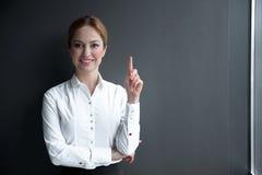 Gladlynt affärskvinna som pekar upp fingret fotografering för bildbyråer