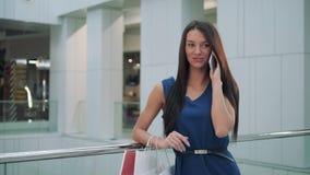 Gladlynt affärskvinna som smsar på den smarta telefonen, medan vänta på hennes flyg i flygplatsterminal shoppinggalleriakvinnasam stock video