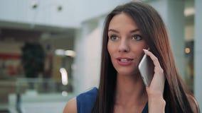 Gladlynt affärskvinna som smsar på den smarta telefonen, medan vänta på hennes flyg i flygplatsterminal shoppinggalleriakvinnasam lager videofilmer