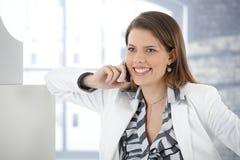Gladlynt affärskvinna som talar på den mobila telefonen arkivfoto
