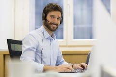 Gladlynt affärsman i kontoret på telefonen, hörlurar med mikrofon, Skype arkivbilder