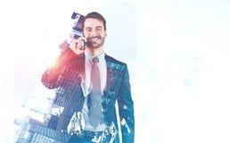 Gladlynt affärsman på smartphonen i stad royaltyfria foton