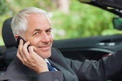 Gladlynt affärsman på telefonen som kör den dyra cabrioleten arkivbild