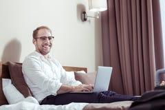 Gladlynt affärsman som bär mörk byxa och den vita skjortan i hotellrum arkivbild