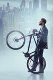 Gladlynt affärsman som cyklar i abstrakt stad Arkivfoto