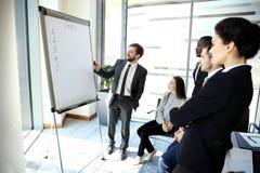Gladlynt affärsman som diskuterar nytt affärsprojekt med medlemmarna av hans lag arkivbilder