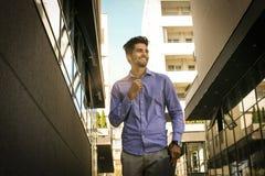 Gladlynt affärsman som går på stadsgatan royaltyfri foto
