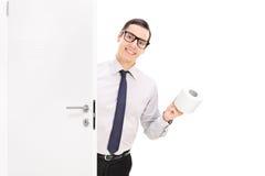Gladlynt affärsman som kommer med toalettpapper Royaltyfri Foto