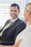 Gladlynt affärsman som ser hans attraktiva blonda kollega Fotografering för Bildbyråer