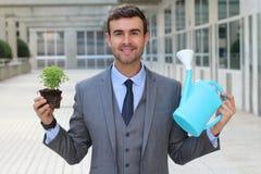 Gladlynt affärsman som tar riktig omsorg av en växt royaltyfria bilder