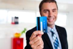 Gladlynt affärsmaninnehav upp hans kreditkort royaltyfri fotografi