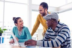 Gladlynt affärsfolk som diskuterar på det idérika kontoret Royaltyfri Fotografi