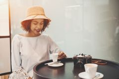 Gladlynt afrikansk amerikanflicka i kafé som dricker kaffe arkivfoto