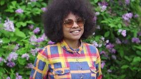 Gladlynt afrikansk amerikankvinna för stående med en afro frisyr på gatan långsam mo stock video