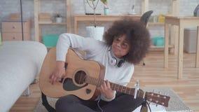 Gladlynt afrikansk amerikankvinna med en afro frisyr med den akustiska gitarren lager videofilmer