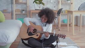 Gladlynt afrikansk amerikankvinna med en afro frisyr med den akustiska gitarren långsam mo lager videofilmer