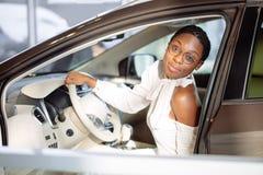 Gladlynt afrikansk kvinnlig chaufför inom bilen Fotografering för Bildbyråer