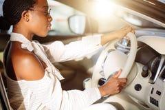 Gladlynt afrikansk kvinnlig chaufför inom bilen Arkivfoton