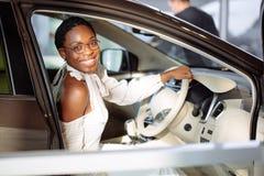 Gladlynt afrikansk kvinnlig chaufför inom bilen Royaltyfri Fotografi
