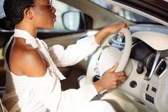 Gladlynt afrikansk kvinnlig chaufför inom bilen Royaltyfria Foton