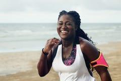 Gladlynt afrikansk löpare som joggar under utomhus- genomkörare på stranden royaltyfri foto