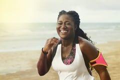 Gladlynt afrikansk löpare som joggar under utomhus- genomkörare på stranden royaltyfria bilder