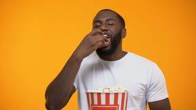 Gladlynt Afro--amerikan man som äter popcorn och ut högt skrattar, komedishow lager videofilmer