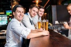 Gladlynt afton för män Fyra vänmän som dricker öl och hav Royaltyfri Foto