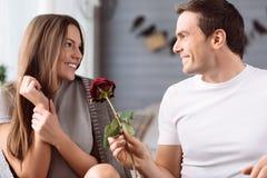 Gladlynt angenäm man som rymmer en blomma fotografering för bildbyråer