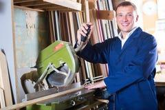 Gladlynt arbetare som klipper träplankor genom att använda cirkelsågen Royaltyfri Fotografi