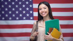 Gladlynt asiatisk flicka som ler med böcker mot USA flaggabakgrund, utbildning lager videofilmer