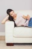 Gladlynt asiatisk flicka som ligger på soffan som läser en tidskrift Royaltyfria Bilder