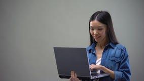 Gladlynt asiatisk kvinna som skriver på bärbar datoranseende på grå bakgrund, freelancer lager videofilmer