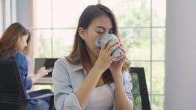 Gladlynt asiatisk ung affärskvinna som i regeringsställning sitter dricka kaffe arkivfilmer