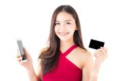 Gladlynt asiatisk ung kvinna med telefonen och kreditkort på vit bakgrund arkivfoto