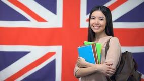 Gladlynt asiatiskt kvinnaanseende mot brittisk flaggabakgrund, studie utomlands lager videofilmer