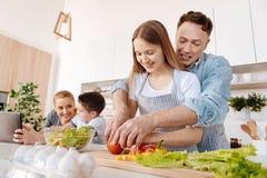 Gladlynt att bry sig fader som undervisar hennes dotter hur man klipper grönsaker arkivfoton
